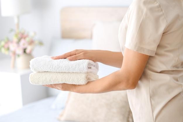 Haushälterin mit sauberen handtüchern im schlafzimmer