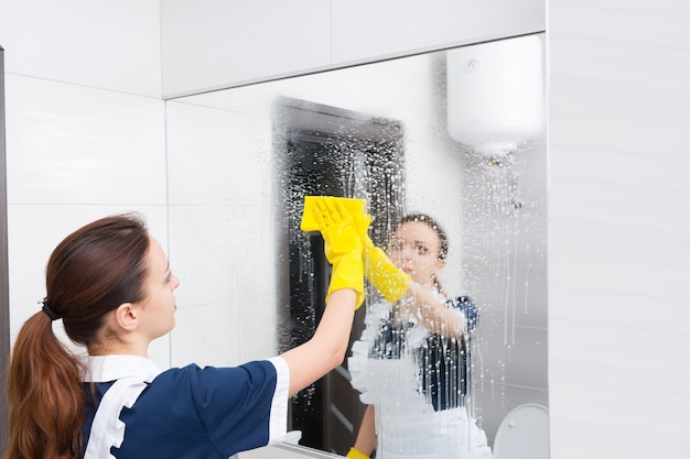 Haushälterin oder zimmermädchen, die einen großen wandspiegel in einem weißen badezimmer reinigen und ihn nach dem besprühen mit reinigungsmittel mit einem tuch abwischen