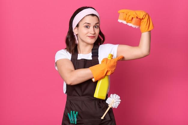 Haushälterin trägt weißes t-shirt und braune schürze und hält schwamm in der hand