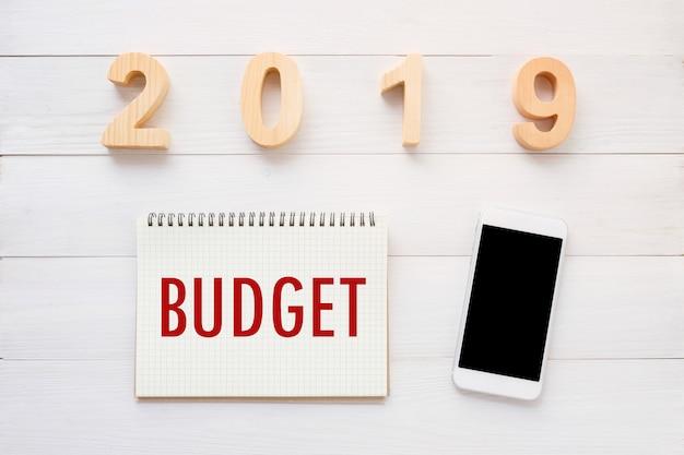 Haushaltswort 2019 auf notizbuchpapierhintergrund und intelligentes telefon auf weißem hölzernem hintergrund