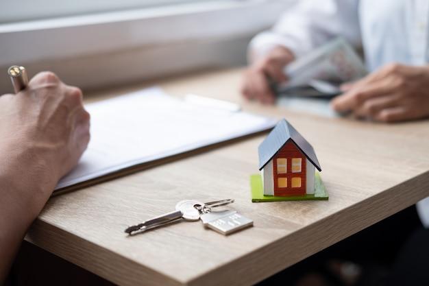 Hauskauf, hand des mannes unterzeichnet einen vertrag, modell eines kleinen hauses und hausschlüssel
