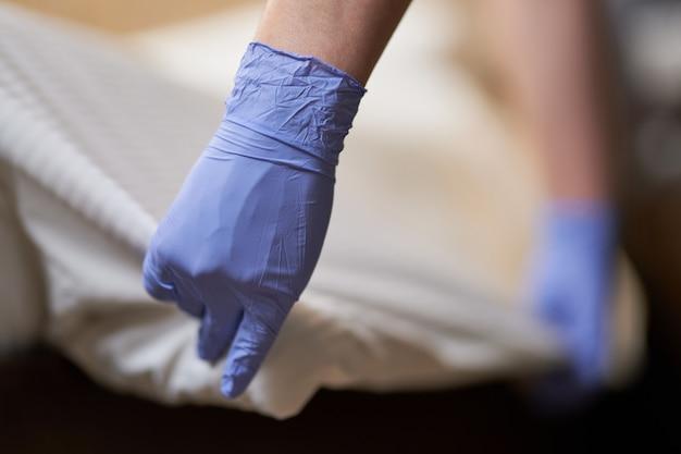 Hausmädchen beim regelmäßigen bettwäschewechsel im zimmer