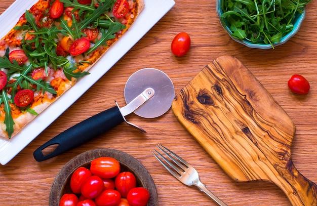Hausmädchen frische pizza mit tomaten, rucola und mozzarell