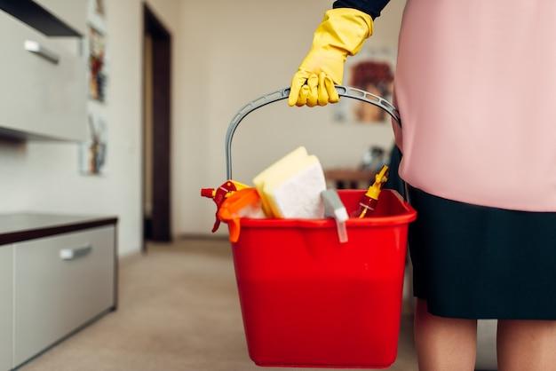 Hausmädchen hände in handschuhen hält reinigungsgeräte, korridor des hotels. professionelle hauswirtschaft, putzfrau