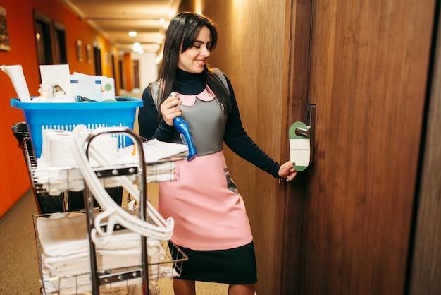 Hausmädchen in uniform beendete die reinigung des zimmers, korridor des hotels. professionelle hauswirtschaft, putzfrau