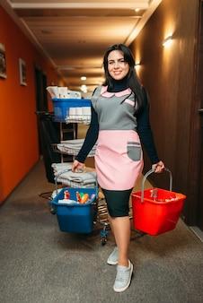 Hausmädchen in uniform hält reinigungsmittel in händen, korridor des hotels. professionelle hauswirtschaft, putzfrau