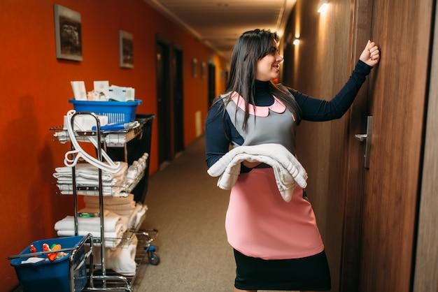Hausmädchen in uniform klopft an die zimmertür, korridor des hotels. professionelle reinigung, putzfrau mit reinigungsgeräten