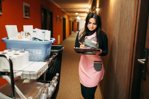 Hausmädchen in uniform macht notizen in notizblock, wagen mit reinigungsmitteln, hotelkorridor interieur. reinigungsservice, professionelle reinigung, putzfrau job