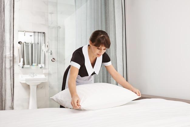 Hausmädchen schlägt kissen im hotelzimmer. porträt einer netten, ordentlichen dame, die als dienstmädchen arbeitet und bett macht, während die eigentümer des hauses abwesend sind, und von jeder oberfläche, die sie sieht, schmutz reinigt und entfernt