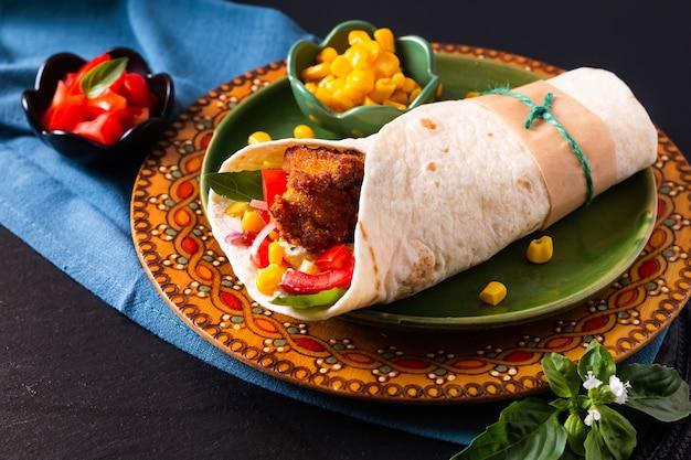 Hausmannskost-konzept bio hausgemachtes gebratenes huhn burrito tortilla sandwich auf farbteller und schwarzem kopierraum