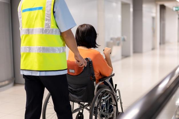 Hausmeister drücken ältere frau auf rollstuhl im flughafenterminal.