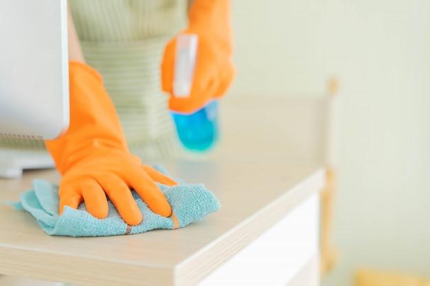 Hausmeister mit mikrofaserstoff auf holztisch streichen, um desktop-tisch zu reinigen