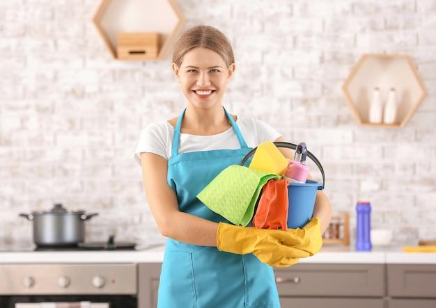 Hausmeisterin mit reinigungsmitteln in der küche