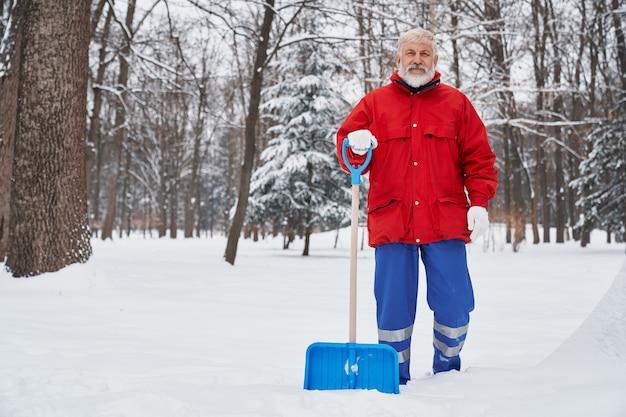 Hausmeisterreinigungsgehweg im park mit schneeschauer.