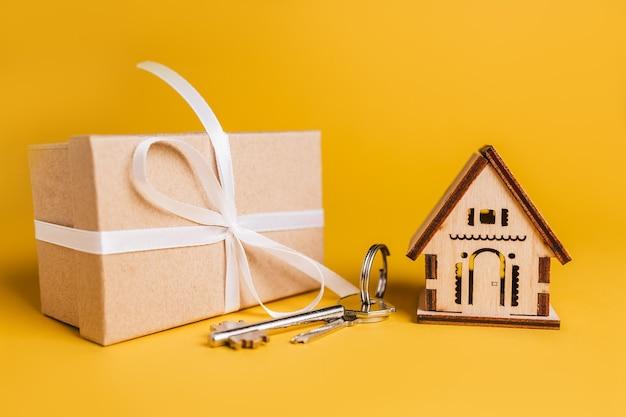 Hausminiaturmodell, geschenk und schlüssel auf gelbem hintergrund. investition, immobilien, haus, wohnen
