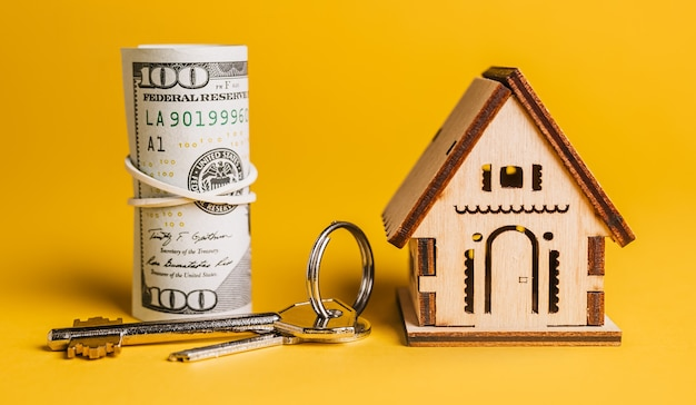 Hausminiaturmodell, schlüssel und geld auf gelbem hintergrund. investition, immobilien, haus, wohnen