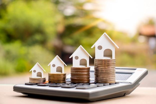 Hausmodell auf einem haufen münzen und unscharfem natürlichen grünen hintergrund. immobilien-investitionsideen hypotheken- und wohnungsbauzinsen