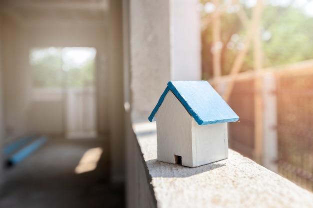 Hausmodell auf fensterrahmen in wohnungsbaustelle