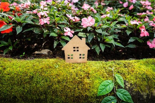 Hausmodell auf grünem gras mit buntem blumenhintergrund