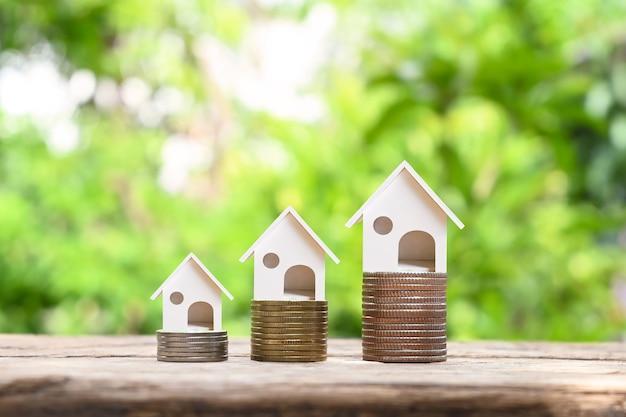 Hausmodell auf haufen von münzen und unscharfem natürlichen grünen hintergrund