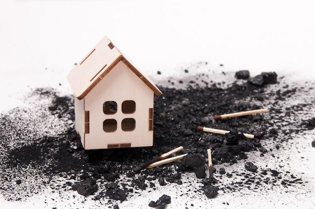 Hausmodell auf kohle und streichhölzer