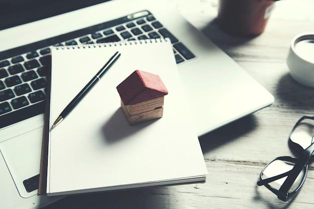 Hausmodell auf notizblock auf laptop