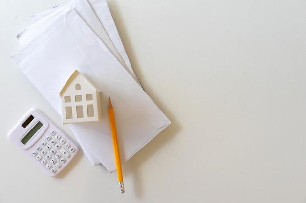 Hausmodell auf postbrief mit taschenrechner und bleistift auf tisch für kosten des wohnungsbaudarlehens