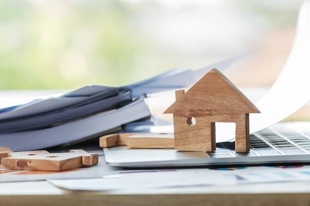 Hausmodell für darlehensimmobilien zum neukauf für familien- oder immobilienhypotheken-investitionskonzept: holzhausmodelle auf laptop-computern mit diagrammberichtsdokumenten, vermögensverwaltung für agentur online.