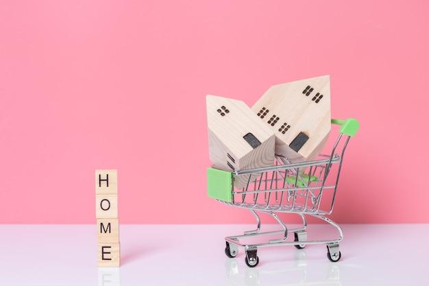 Hausmodell im einkaufswagen und wort haus gemacht von den holzklötzen auf rosa hintergrund mit kopienraum.