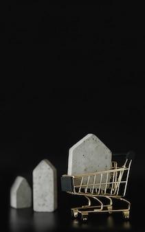 Hausmodell im mini-einkaufswagen auf schwarzem hintergrund kaufen sie ein haus freier platz für text