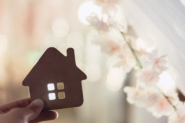 Hausmodell in der hand der hausversicherungsmakleragenten oder in der verkäuferperson.