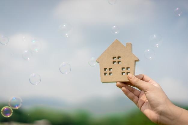Hausmodell in der hand des hausversicherungsmakleragenten oder in der verkäuferperson und -blasen.