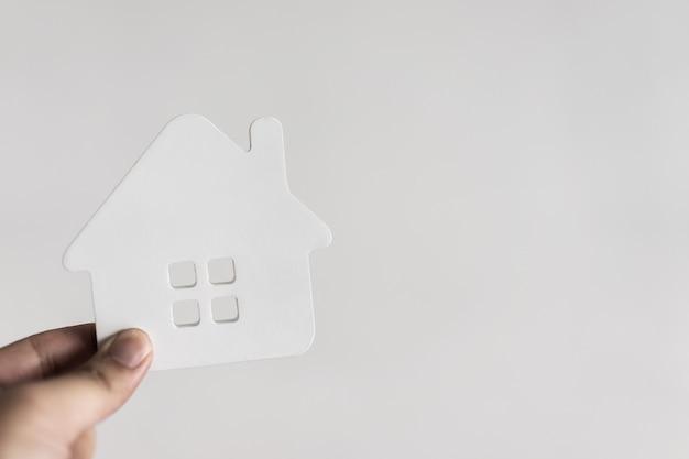 Hausmodell in der hand des hausversicherungsmaklers