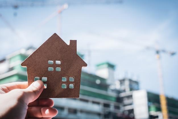 Hausmodell in der hausversicherungsmakleragentenhand oder in der verkäuferperson.