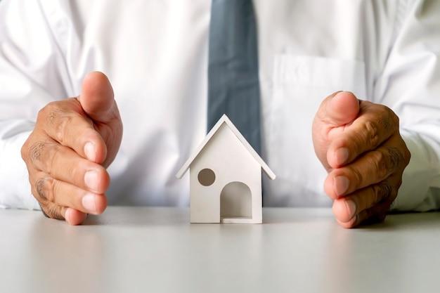 Hausmodell in männlichen geschäftshänden, immobilienkonzept, finanzierung, kreditaufnahme und hypothek.