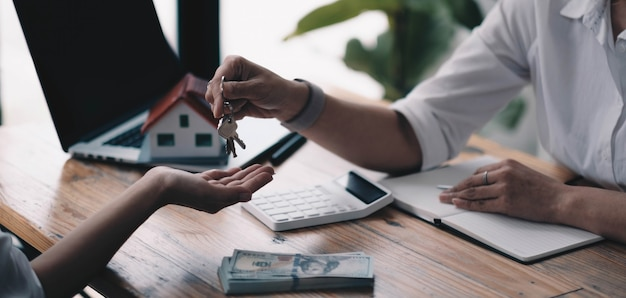 Hausmodell mit agent und kunde, die über einen vertrag zum kauf, zum erhalt einer versicherung oder zum darlehen von immobilien oder eigentum diskutieren.