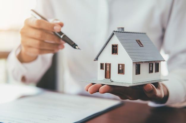 Hausmodell mit der immobilienagentur und kunden, die sich besprechen, damit vertrag haus kauft