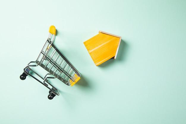 Hausmodell mit einkaufswagen. immobilienkauf eines hauskonzepts.