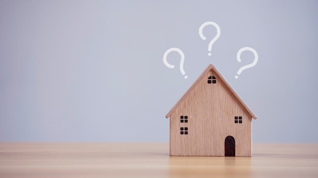 Hausmodell mit fragezeichen auf dem tischhintergrund, der den kauf einer immobilie plant