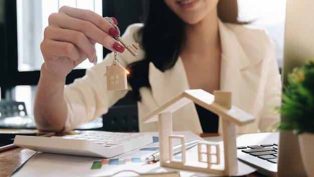 Hausmodell mit immobilienmakler, der für vertrag zum kauf des hauses bespricht.