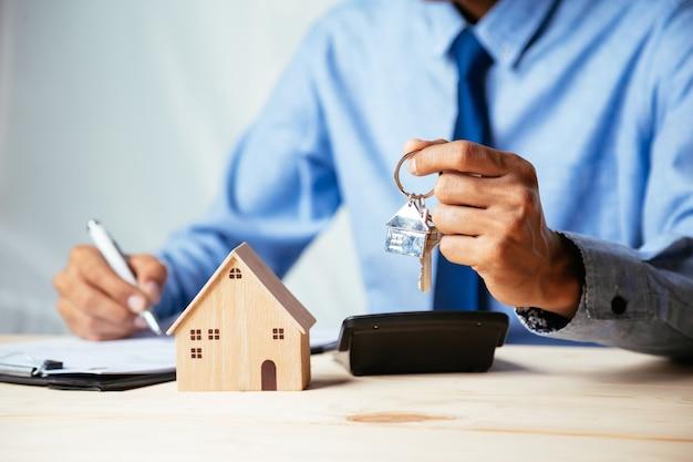 Hausmodell mit immobilienmakler und kunden, die über einen vertrag zum kauf von haus-, versicherungs- oder darlehensimmobilien diskutieren, immobilienkonzept.