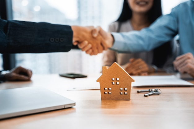 Hausmodell mit immobilienmakler und kundenvertrag zum kauf von haus und händedruck nach kontaktaufnahme
