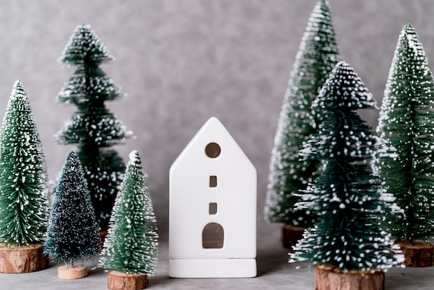 Hausmodell mit weihnachtsbaum und grauem ledernem hintergrund