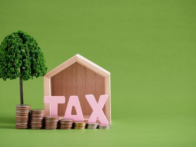 Hausmodell mit wortsteuer und münzen auf grünem hintergrund. platz für text