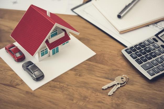 Hausmodell, schlüssel und taschenrechner mit dokumenten auf dem tisch