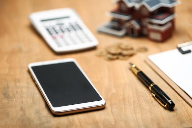 Hausmodell, smartphone, taschenrechner und goldene münzen auf holztisch
