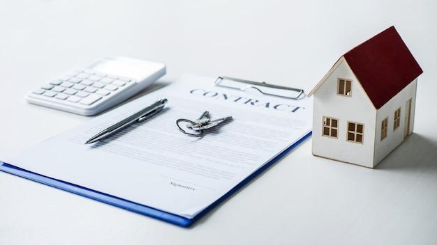 Hausmodell, taschenrechner und hausschlüssel, die auf immobilienvertrag liegen