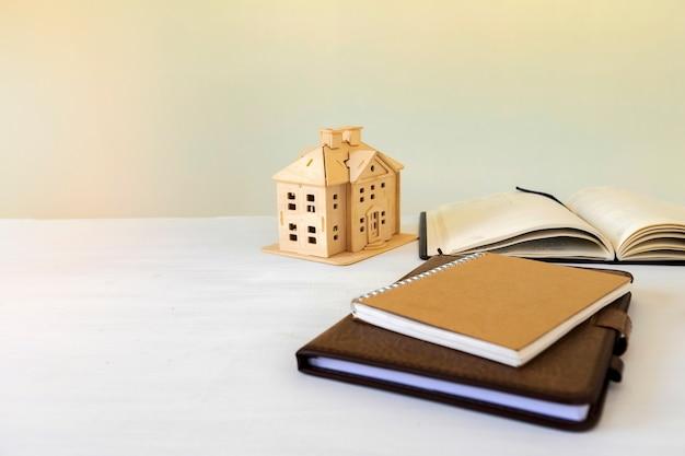 Hausmodell und buch auf dem schreibtisch. immobilien-konzept