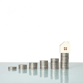 Hausmodell und münzengeld auf tabelle für finanz- und bankwesenkonzept.