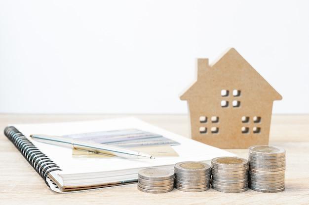 Hausmodell und notizblock mit münzen auf dem tisch